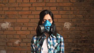 The woman wearing the mask of air pollution from traffic, on a brick background . She's looking at the camera. Shallow depth of field.