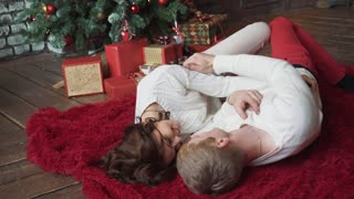The young couple fall to the floor in a cozy house on the Christmas tree.