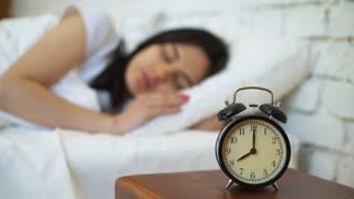 Tired brunette turning off her alarm clock in her bedroom.
