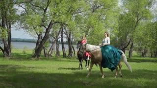 Walk of the girls on horseback in the woods