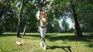 Woman doing fitness exercises outdoor. Female runner stretching before running marathon in green forest. Slim girl in sports clothes doing stretching exercises in park. Outdoor workout