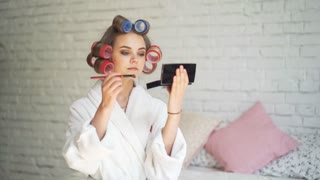 Woman in hair curlers applying mascara indoors at home