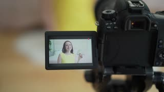 Woman in yellow dress talking in front of camera to make a video blog.