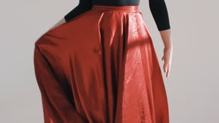 Woman posing in a fluttering red skirt. Red cloth fluttering.