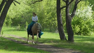 Woman riding horseback through forest