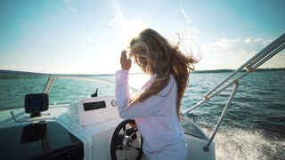 Woman sitting in boat, hair blowing in the wind, celebrating scenic landscape, nature, sea view, enjoying rest