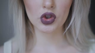Women's lips are colored with dark lipstick. Kiss close-up