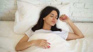 Young attractive woman lying in the bed, enjoying the morning at home. Girl looking at the camera and smiling.