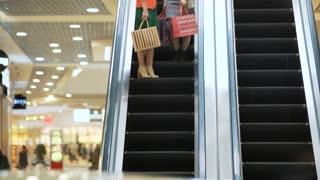Young beautiful happy women on escalator of shopping mall