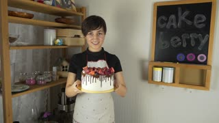 Young beautiful woman in an apron making cake with cream and berries at the kitchen