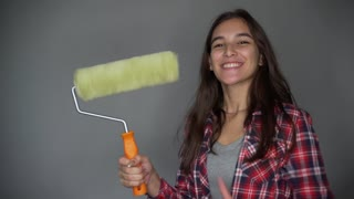 Young beautiful woman in casual clothes smiling holding paint roller for wall painting isolated on grey background. Tools, accessories, tools to repair the apartment room. Home repair