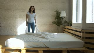 Young beautiful woman making bed