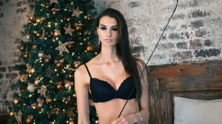 Young beautiful woman sitting on the bed near the Christmas tree. Brunette girl in black lingerie.