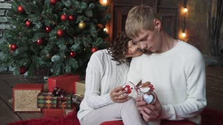 young couple, man and woman, smiling, happy, wearing Christmas decoration, holding new years toys.