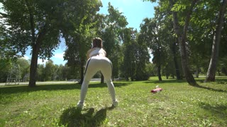 Young female athlete doing squat exercises outdoors in park. Fit girl working out her core and glutes with bodyweight.