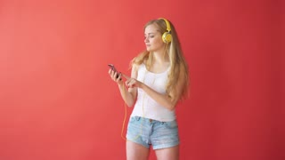 Young pretty caucasian woman holding mobile phone and listening music with earphones over red background