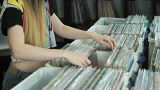 Young woman looking at old vinyl records at flea market