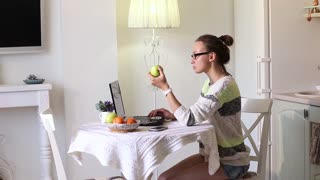 Woman eating fruit while working on computer in office