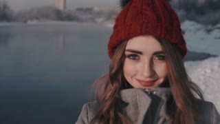 young beautiful woman throwing snow at camera and smiling
