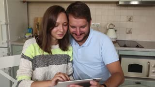 Young couple in kitchen looking at tablet pc. Man standing by his girlfriend sitting using digital tablet in morning.