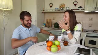 Young couple talking while having meal in kitchen at home. Conversation between a man and a woman