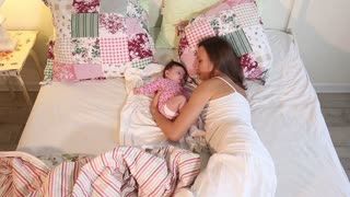Young mother playing with her little baby on the bed - indoors