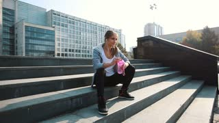 Young sports woman having a break on the stairs with bottle of water after the morning jogging in the modern city. Healthy lifestyle in the big city.