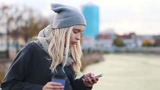 Young woman drinking coffee and talking on the mobile phone. Woman talking via mobile phone and holding a coffee paper cup on the urban street background.