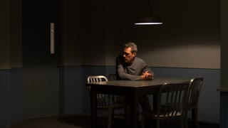 ANXIOUS MAN ALONE IN AN INTERROGATION ROOM