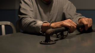 CLOSE UP - MAN HANDCUFFED TO INTERROGATION ROOM TABLE