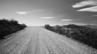 DRIVING A DESERT ROAD IN THE AMERICAN WEST.  SHOT IN B & W.