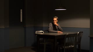 MAN IN CUSTODY WAITS IN AN INTERROGATION ROOM