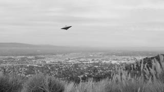 UFO FLIES OVER AN URBAN VALLEY.  BLACK & WHITE FOOTAGE OF A FLYING SAUCER.