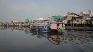 BOAT POV WS PAN Boat Floating Along River with Houses Along Bank / Hoi An, Vietnam