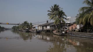 BOAT POV WS PAN Riverbank with Footbridge and Houses / Vietnam