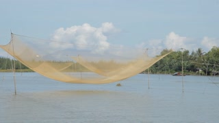 BOAT POV WS Traditional Fishing Net Resting Above Water / Vietnam
