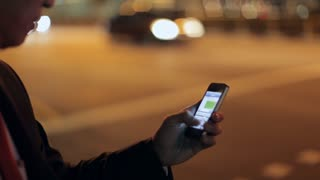 CU Businessman Texting on Phone near Street with Cars Going by at Night / Singapore