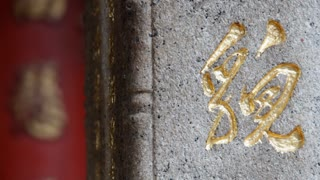 CU Gold Chinese symbol etched onto stone wall / Hong Kong, China