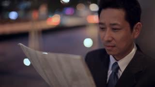 CU LD Businessman Reading Newspaper in Evening / Singapore