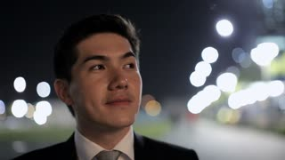 CU LD Businessman Smiling at Night with Street Lights Behind / Singapore