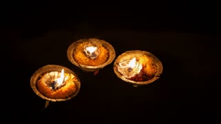 CU Lit candles floating on water at night / India