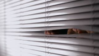CU Man opening blinds and looking out