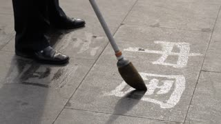 CU Man writing Chinese calligraphy on pavement with water / Beijing, China