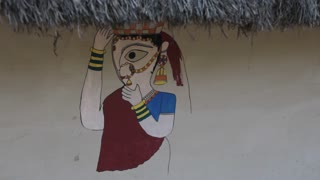 CU Painting of woman on thatched house / India