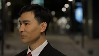 CU Portrait of businessman smiling and nodding, standing on street at night / China
