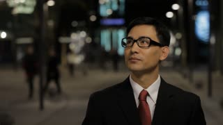CU Portrait of businessman taking off his glasses and smiling, standing on street at night / China