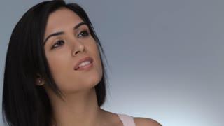 CU Portrait of young woman applying make up, studio shot