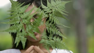 CU Portrait of young woman covering face with fern leaves / Singapore