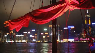 CU R/F Red Boat sails in foreground of harbor view / Hong Kong, China