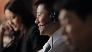 CU SELECTIVE FOCUS Customer service representatives talking in office, focus on man talking on headset / China